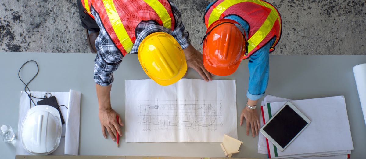 Top view of group of engineering team is meeting, planning construction work,looking paper plans at construction site,overhead view,Concept for team work